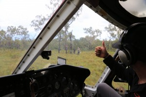 Flying in the wet season: helicopter pilot Mitch Ballantyne gives the thumbs up for a team to approach the chopper.